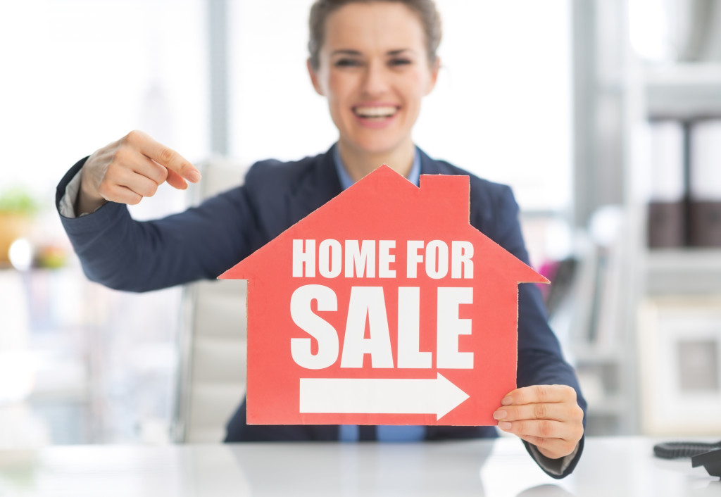 Closeup on happy realtor woman pointing on home for sale sign